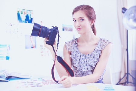 Portrait of a young beautiful photographer woman near table Stock Photo