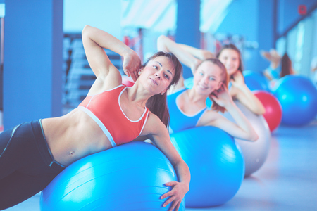 Sporty people sitting on exercise mats at a bright fitness studio. Sporty girls 스톡 콘텐츠
