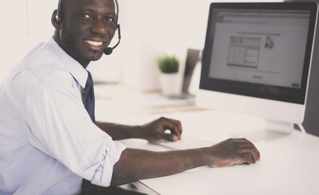 African american businessman on headset working on his laptop Imagens - 115632189