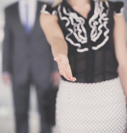 Businesswoman shaking hands in office .