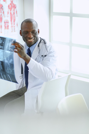 Portrait young african medical doctor holding patients x-ray
