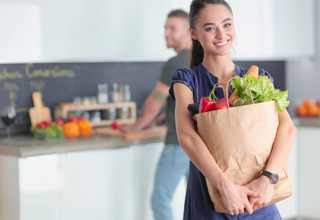 Young couple in the kitchen , woman with a bag of groceries shopping 写真素材