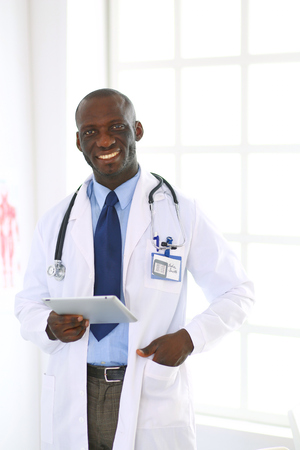 Male black doctor worker with tablet computer standing in hospital