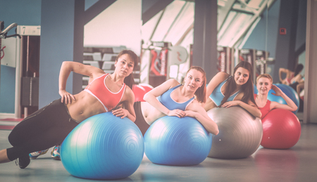 Sporty people sitting on exercise mats at a bright fitness studio. Sporty girls Stock Photo
