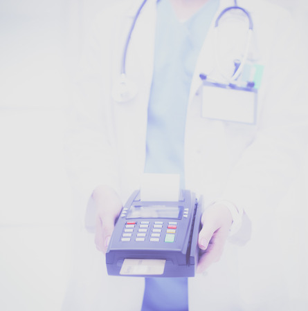 Doctor is holding payment terminal in hands. Paying for health care. Doctor Stock Photo