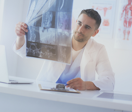 Handsome doctor is talking with young female patient and making notes while sitting in his office. Stock Photo