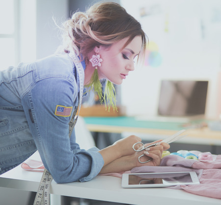 Fashion designer woman working with ipad on her designs in the studio Stock Photo