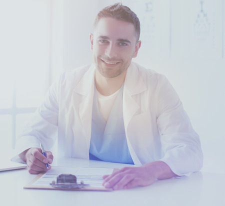 Portrait of a male doctor with laptop sitting at desk in medical