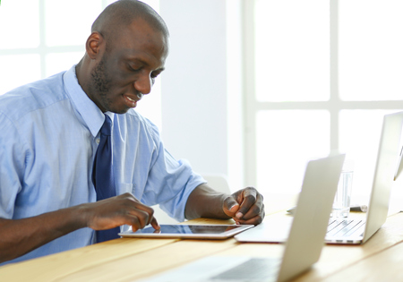 African american businessman on headset working on his laptop