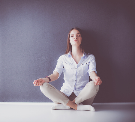 Portrait of a casual happy woman sitting on the floor on gray background