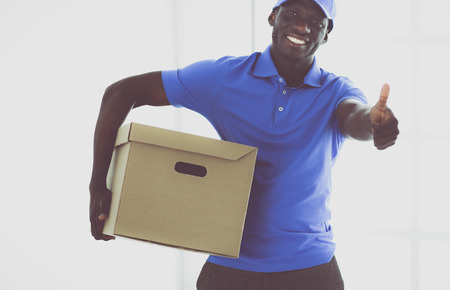 Portrait of an handsome happy deliverer with box