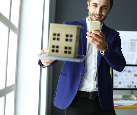 Businessman holding house miniature on hand standing in office. 版權商用圖片