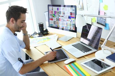 Portret młodego projektanta siedzącego w studiu graficznym przed laptopem i komputerem podczas pracy online. Zdjęcie Seryjne