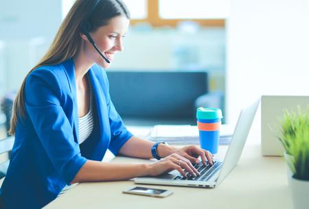 Ritratto di bella donna d'affari che lavora alla sua scrivania con auricolare e laptop..