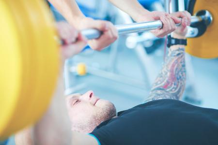 Bodybuilder with barbell in gym. Bodybuilder