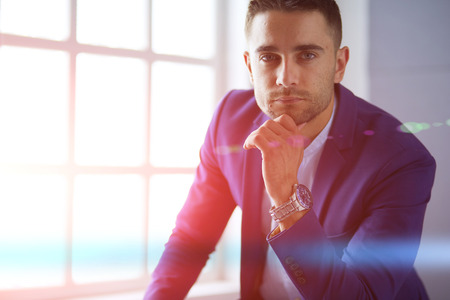 Young businessman sitting isolated on grey background Stock Photo