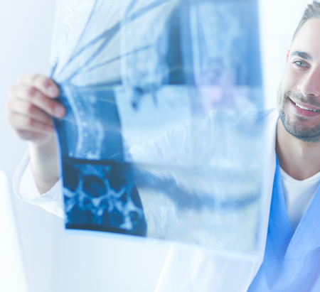 Young doctor sitting at his office desk and analyzing an x-ray Stock Photo