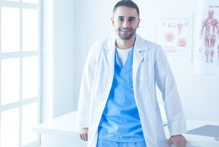 Young and confident male doctor portrait standing in medical office