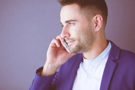 Attractive young man with smartphone on color background