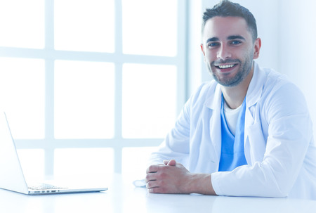 Portrait of a male doctor with laptop sitting at desk in medical office Stock Photo