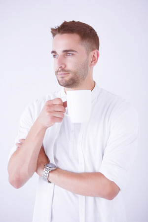 Young business man drinking a cup of coffee or tea Stock Photo