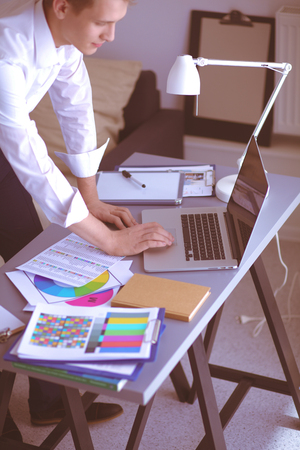 Young businessman working in office, standing near desk Stock Photo