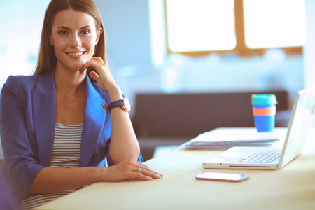 Woman sitting on the desk with laptop Stock Photo
