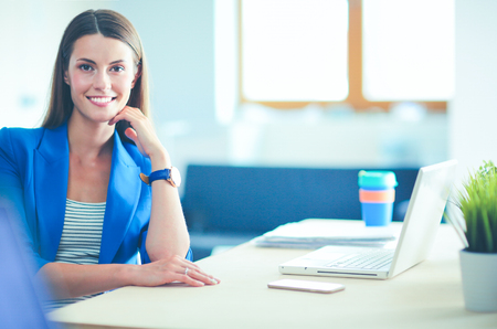 Woman sitting on the desk with laptop. Stock Photo