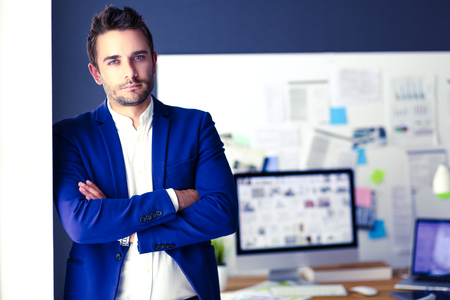 Portrait of young designer in front of laptop and computer while working. Stock Photo