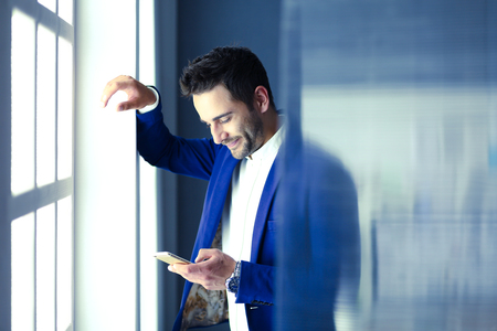 Business man in suit talking on phone and looking away near the window.