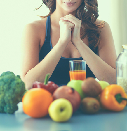 Girl sitting in kitchen on the desk with fruit and glasses juice Stock Photo