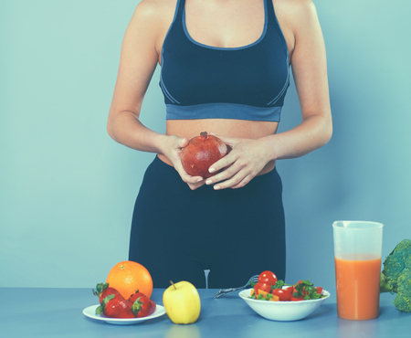 Young and beautiful woman standing near desk with vegetables Stock Photo