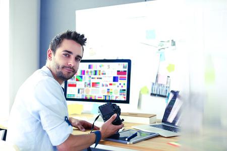 Portret van jonge ontwerper zit op grafische studio voor laptop en computer tijdens het online werken. Stockfoto