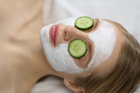 Beautiful young woman receiving facial mask of cucumber in beauty salon