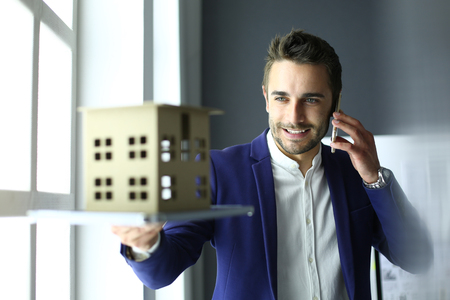 Businessman holding house miniature on hand standing in office. Banco de Imagens