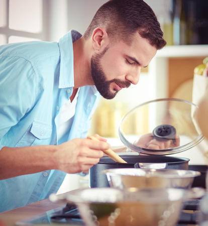 Man following recipe on digital tablet and cooking tasty and healthy food in kitchen at home Stock Photo