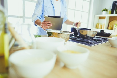 Man following recipe on digital tablet and cooking tasty and healthy food in kitchen at home.