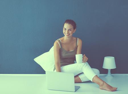 Attractive caucasian girl sitting on floor with laptop Imagens - 122796895