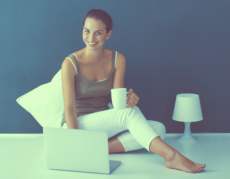 Attractive caucasian girl sitting on floor with laptop