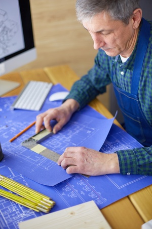 Architect working on drawing table in office 免版税图像