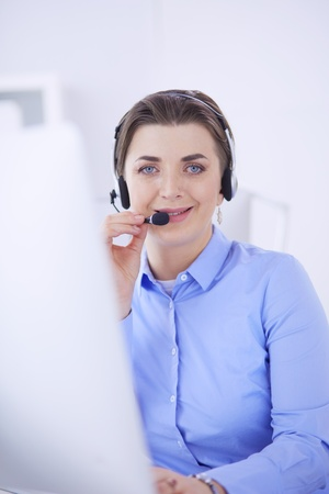 Serious pretty young woman working as support phone operator with headset in office Stockfoto - 122798023