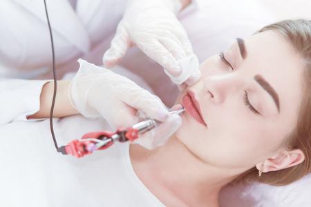 Een jong meisje met rode lippen permanente make-up, micropigmentatie Stockfoto