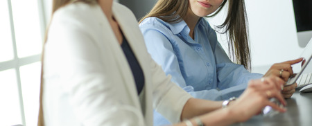 Two female colleagues in office sitting on the desk