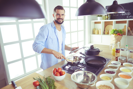 Man following recipe on digital tablet and cooking tasty and healthy food in kitchen at home Standard-Bild