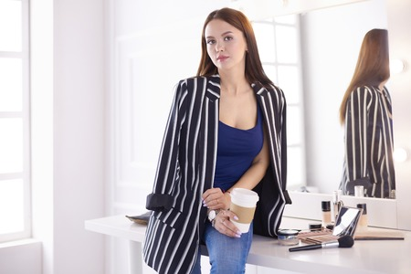 Stylish female make up artist drinking cup of cappuccino and waiting for visitors at modern interior Stock Photo