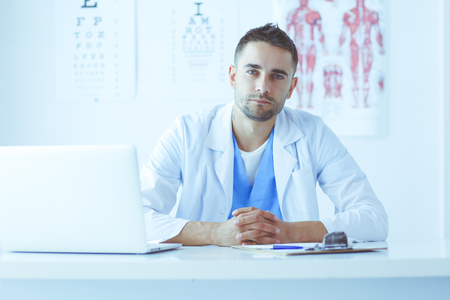 Portrait of a male doctor with laptop sitting at desk in medical office Stock fotó