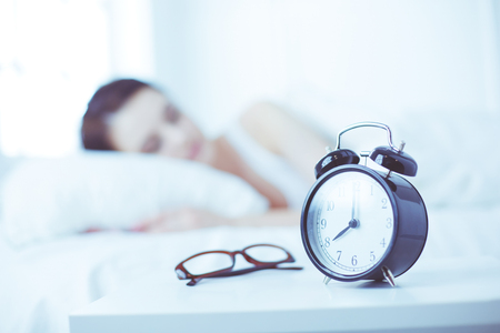 Beautiful young woman sleeping while lying in bed comfortably and blissfully on the background of alarm clock