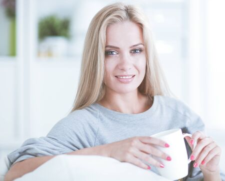 A woman sitting on the couch with a cup in her hands and smiling as she looks in front of her
