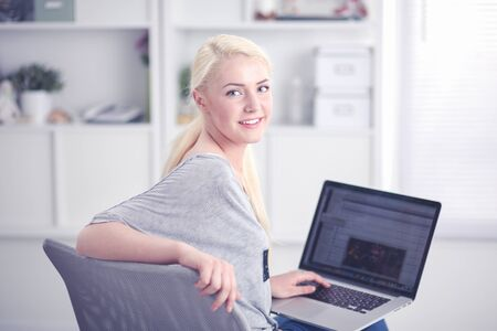 Beautiful young blond woman at home sitting on sofa or settee using her laptop computer Stockfoto