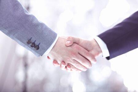 Zbliżenie dłoni biznesmena wstrząsnąć bizneswoman między dwoma kolegami OK, odnieść sukces w biznesie